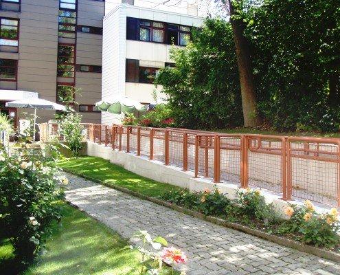 Umsetzung der ÖNORM 1500 - Rampe aus Sichtbeton, Schlosserabeiten und Pflasterung an Bestand angeglichen