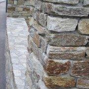 Einfriedung aus Pfeilern mit Naturstein und Trockenmauer